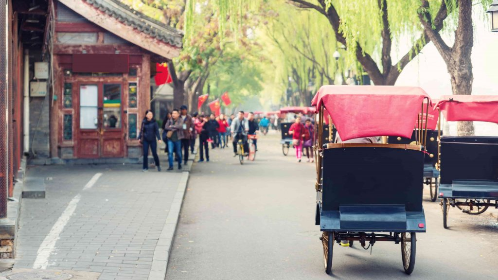 Tourists-riding-Beijing-traditional-rickshaw-in-old-China-Hutongs-in-Beijing-China-min