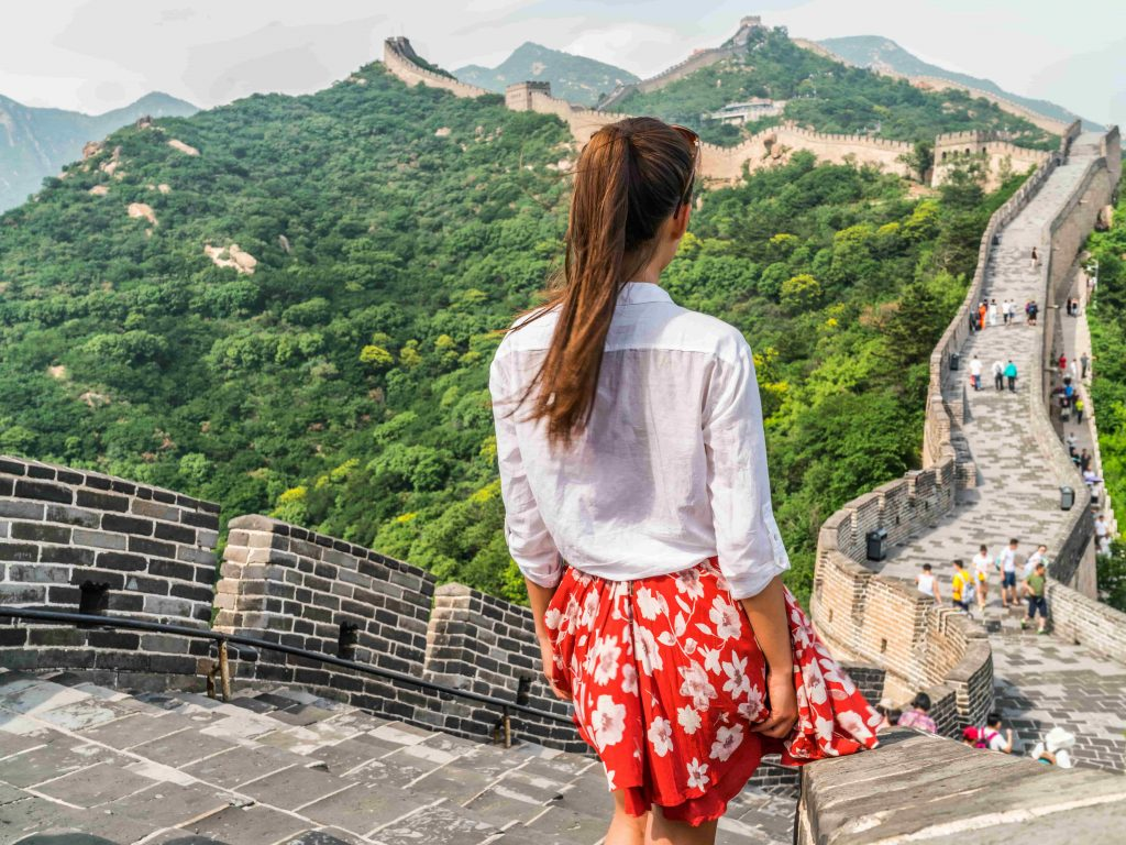 oung-girl-tourist-from-behind-looking-at-view-of-Great-Wall-of-China-at-famous-Badaling-tourism-attraction-during-travel-vacation-in-Beijing.-Asia-summer-holidays.-min
