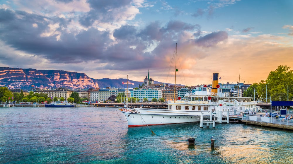 Panoramic-view-of-the-historic-city-center-of-Geneva-with-traditional-paddle-steamer-boat-on-Lake-Geneva-in-beautiful-golden-evening-light-at-sunset-with-blue-sky-and-clouds-in-summer-Switzerland